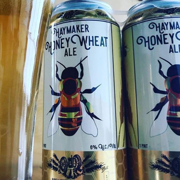 Haymaker Honey Wheat cans with large bee in the center