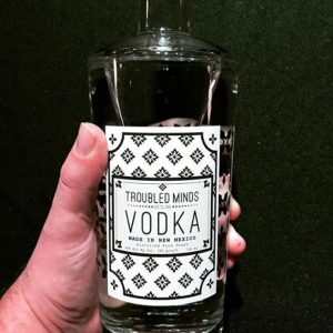 Hand Holding bottle of Troubled Mind Vodka