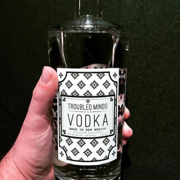 Hand Holding bottle of Troubled Mind Vodka